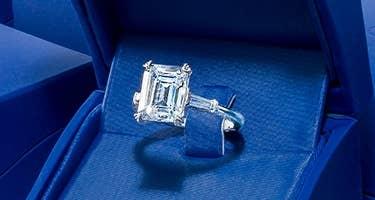 Emerald cut engagement ring in an open Tacori blue box
